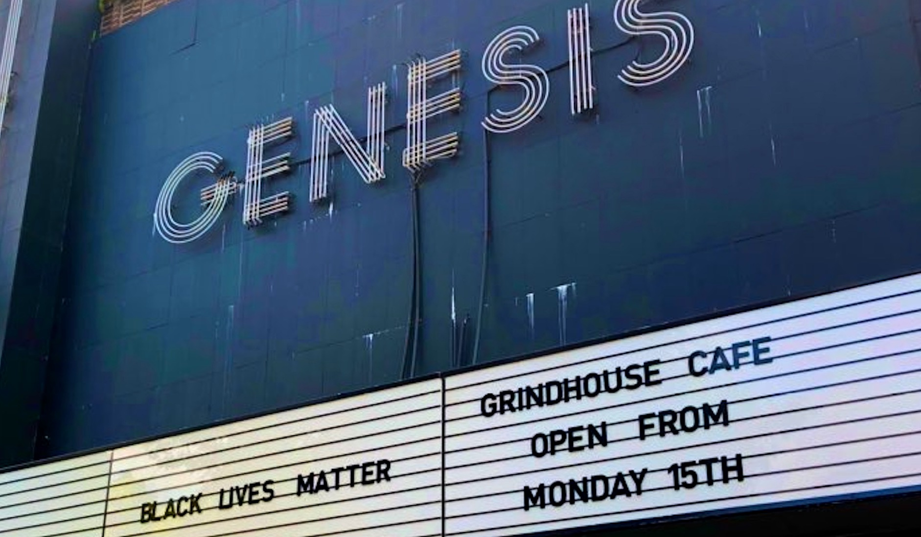 "This is a photograph of the front of Genesis Cinema showing their sign reading ""grindhouse cafe reopening 15 June""."